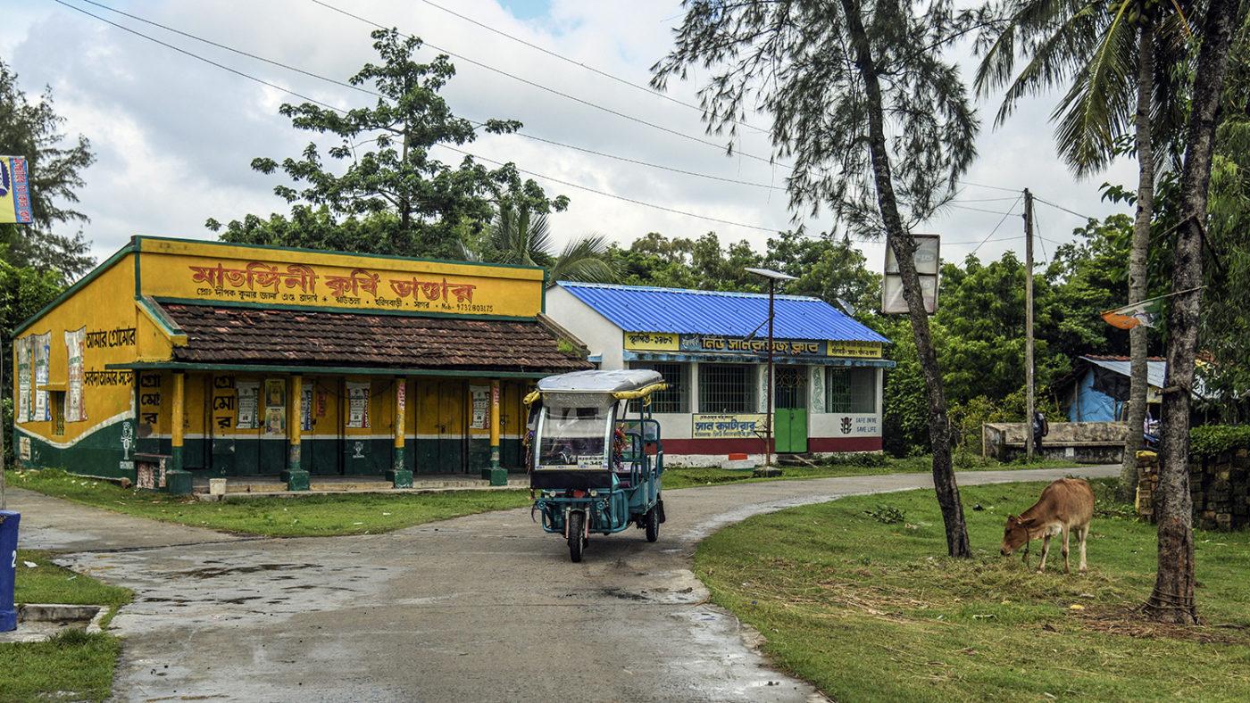 En tuktuk kjører langs veien.