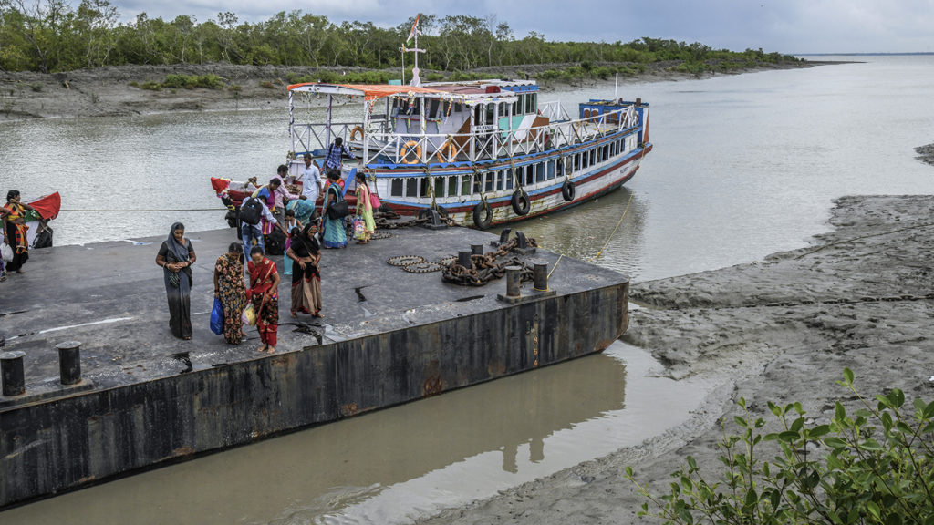 People getting off a boat at a dock.