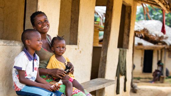 Sia og barna hennes smiler etter en øyescreening i Liberia.