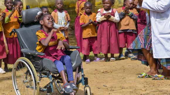 Lesline, som er rullestolbruker, sammen med klassekameratene på den inkluderende skolen hennes i Kamerun.
