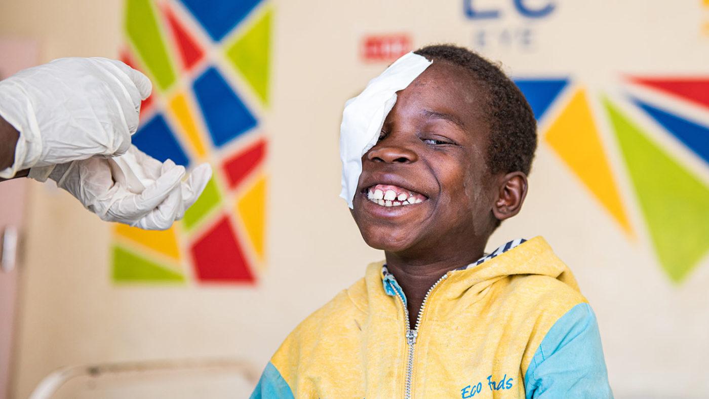 Gutten smiler fra øre til øre etter at bandasjene er fjernet fra øynene.