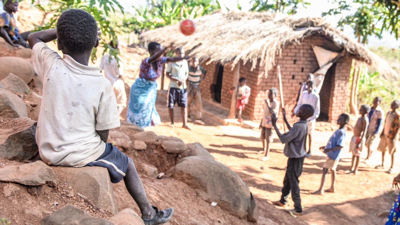 Taonga sitter på sidelinjen og ser på andre barn som leker med ball.