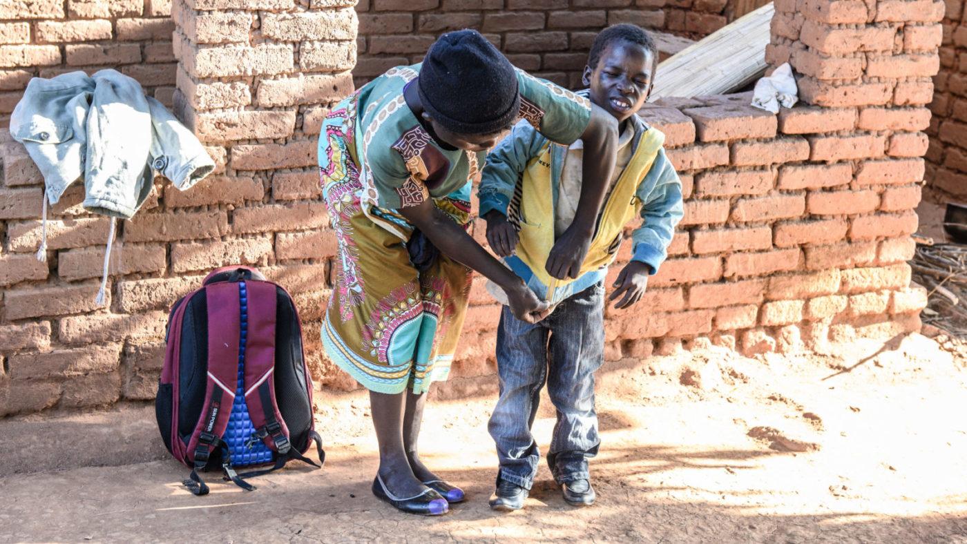 Zelina lukker jakken for gutten sin. Taonga har det vanskelig.
