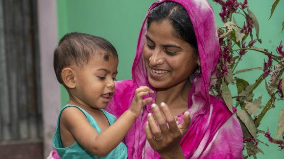 En ung smilende kvinne med en baby i armene.