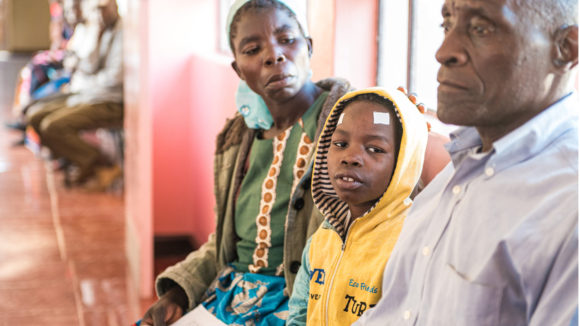 Zelina trøster den åtte år gamle gutten sin mens de står i kø på sykehuset.