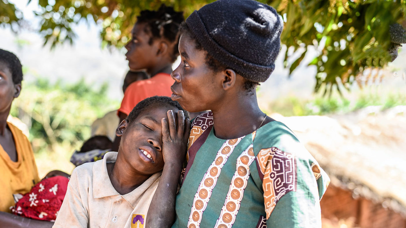 Åtte år gamle Taonga lener seg mot moren, holder hånden sin mot øyet.