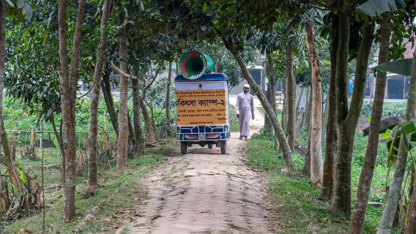 En megafon-moped kjører gjennom en gate i Bangladesh.
