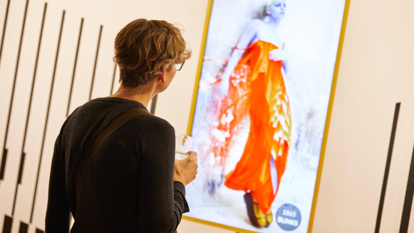 En kvinne betrakter kunst som oppløses i et kunstgalleri