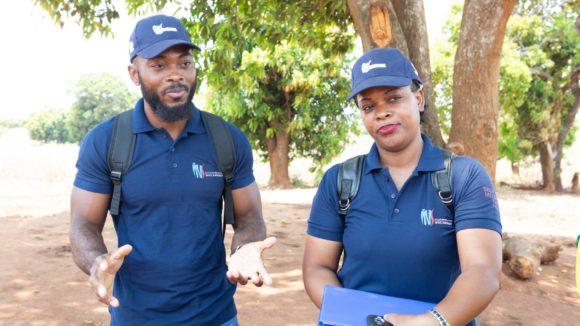 En mann og kvinne står utenfor før oppstarten av undersøkelser i forbindelse med kartlegging av elveblindhet.