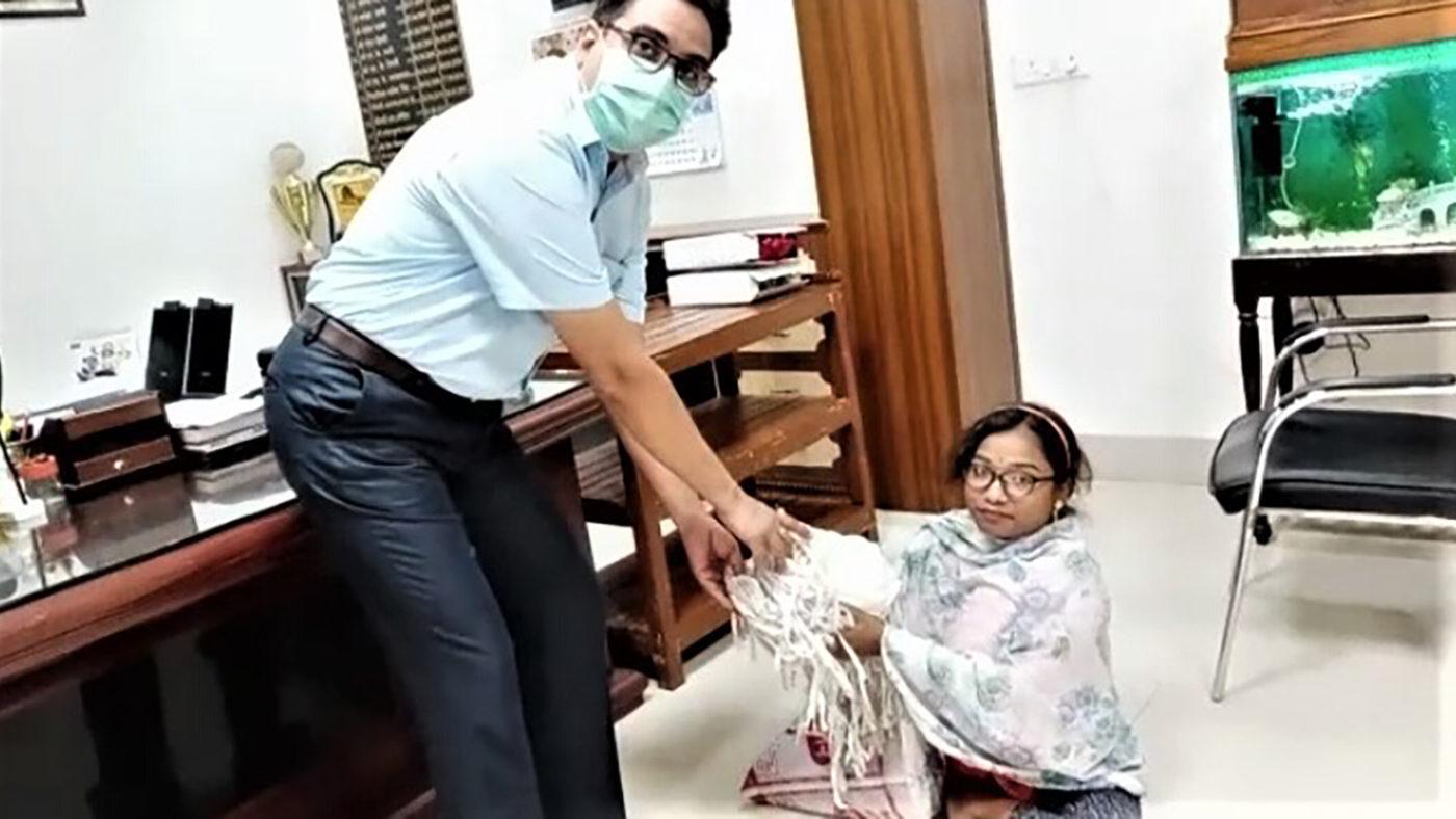 En dame med nedsatt funksjonsevne leverer masker til en klinikk.