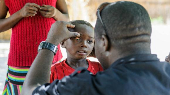 En trakom-lege fra Sightsavers undersøker øynene til beboere i en landsby i et øde område.