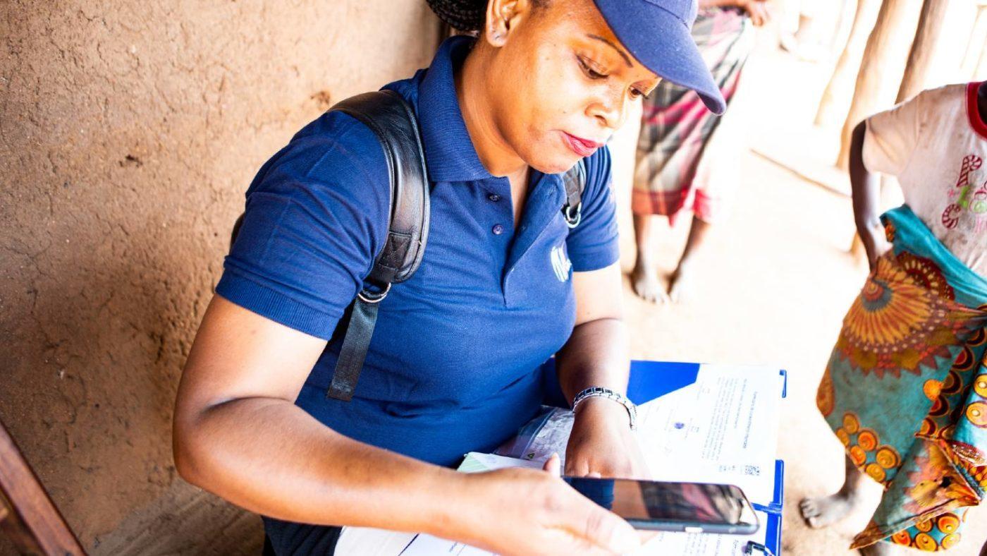 En kvinne bruker mobiltelefon til å registrere data.