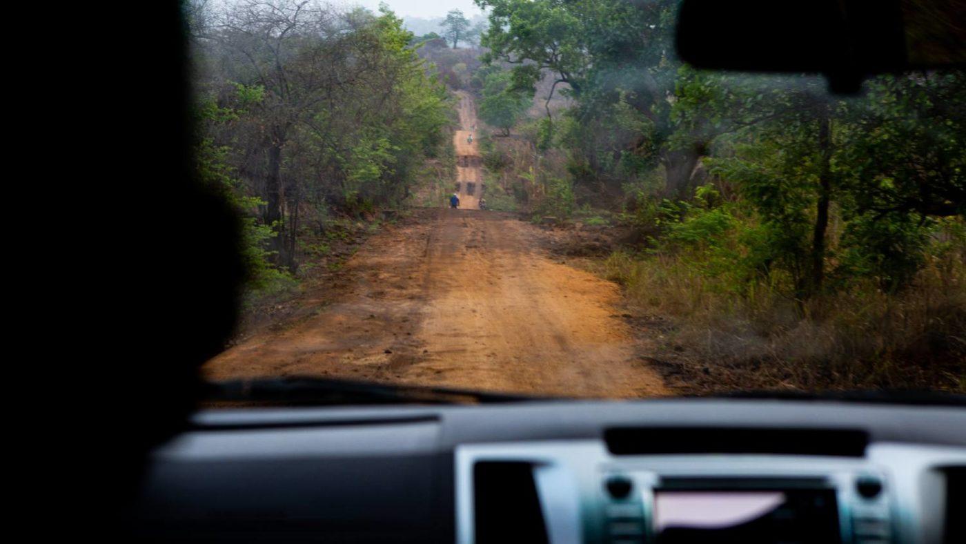 En humpete grusvei i Zambezi-provinsen sett gjennom frontruten på en bil.