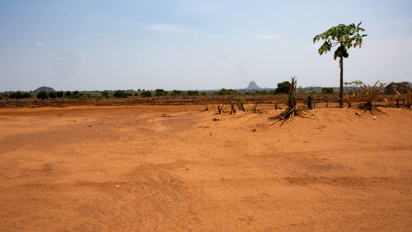Landskapsfoto viser fjell i bakgrunnen av en landsby i Zambezi, Mosambik.