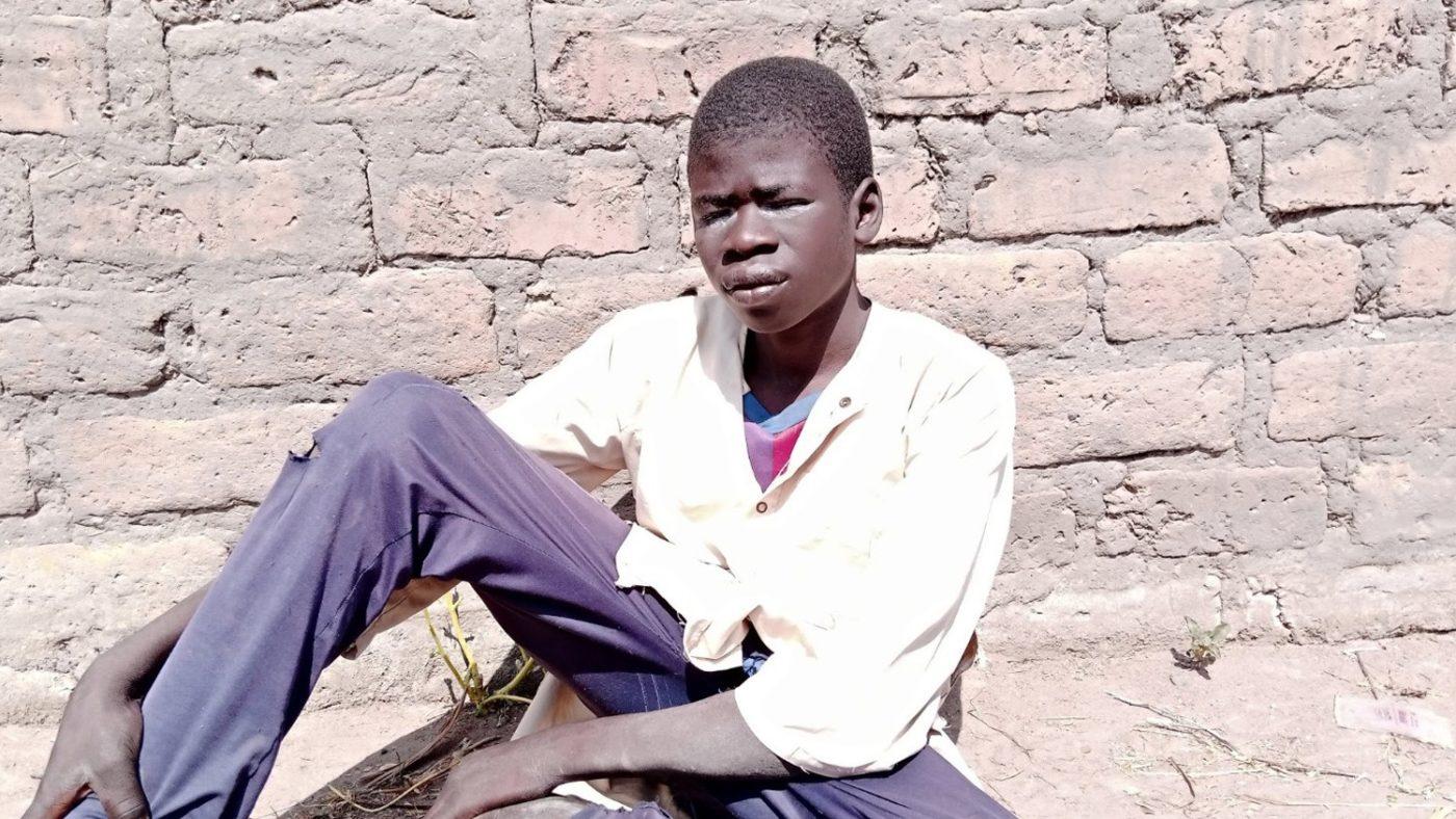En tenåring som lider av trichiasis, sittende ved en mur.