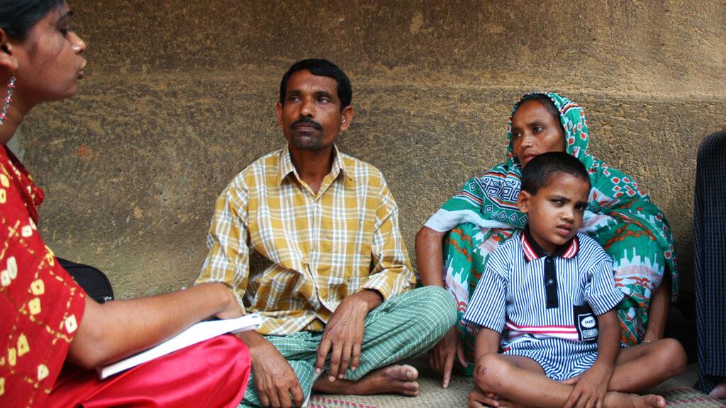 En ung gutt sitter på gulvet med familien.