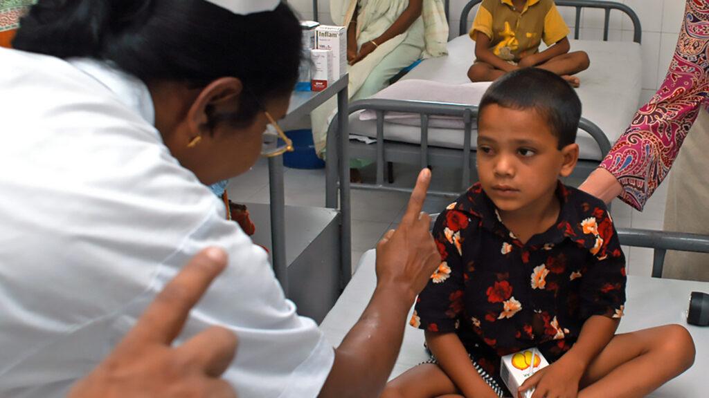 En lege sjekker øynene til en gutt.