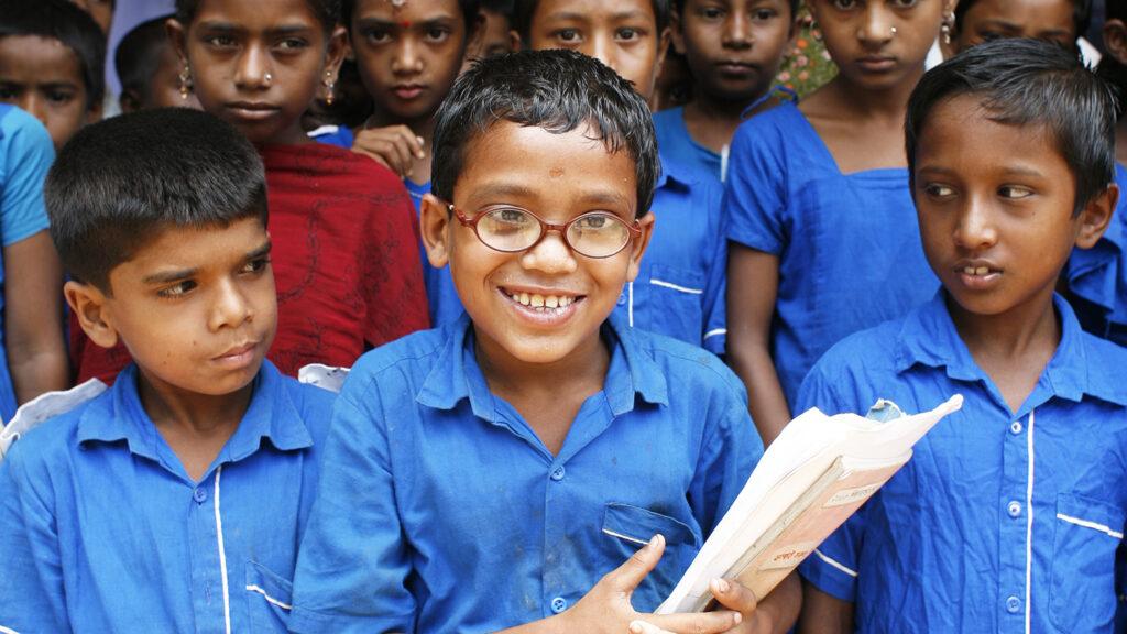 En gutt med briller smiler på skolen.