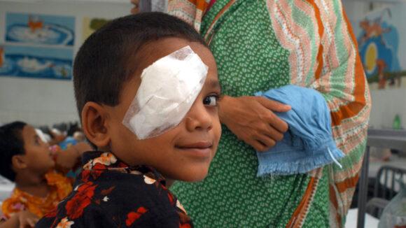 Arif smiler mot kameraet, øyet dekket av et bandasje.