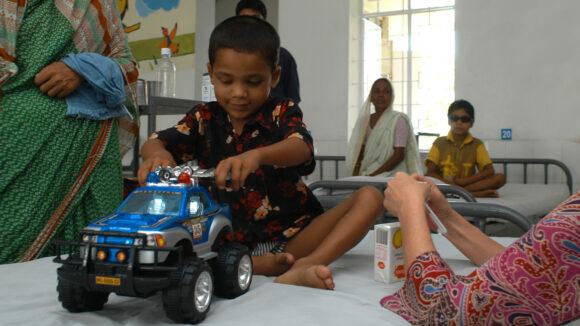 Arif leker med en blå lastebil.