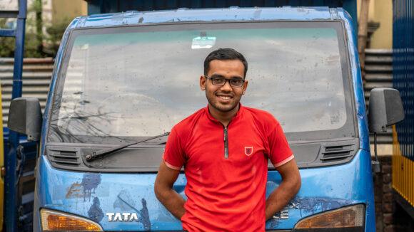 Arif står foran lastebilen han kjører på jobb.