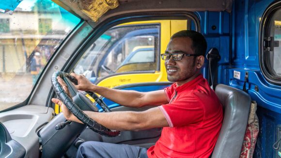 En ung mann som sitter i førersetet til en varebil.