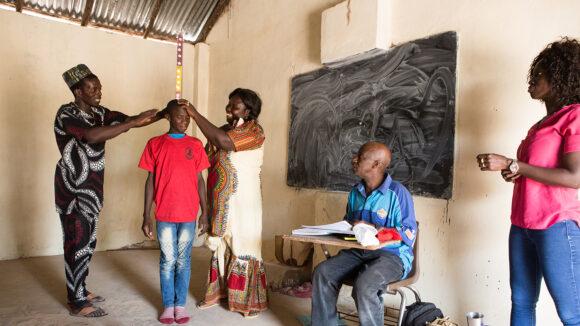 En dreng i skolealderen måler sin højde for at få ormekurbehandling under en skolebaseret massemedicinadministration.