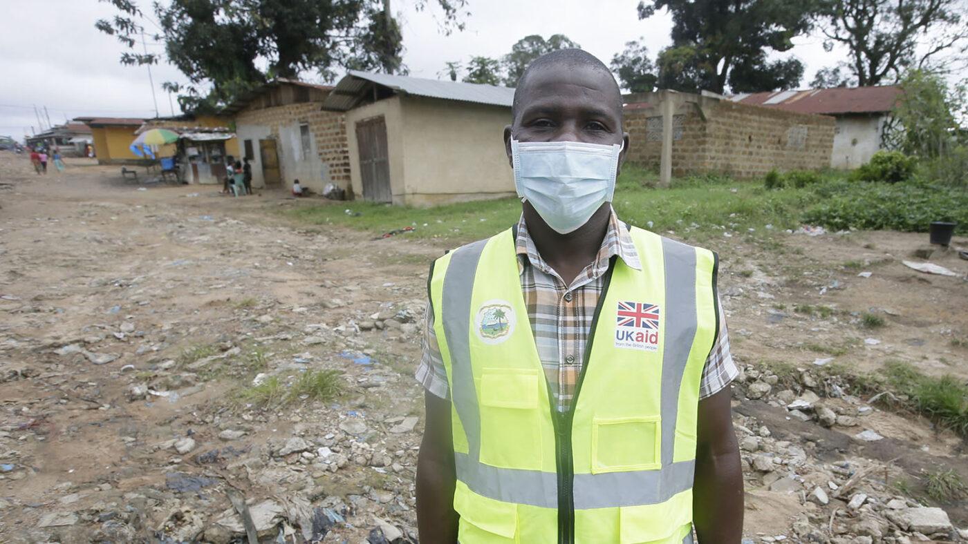 En mann står for et portrett mens han har på seg en maske.