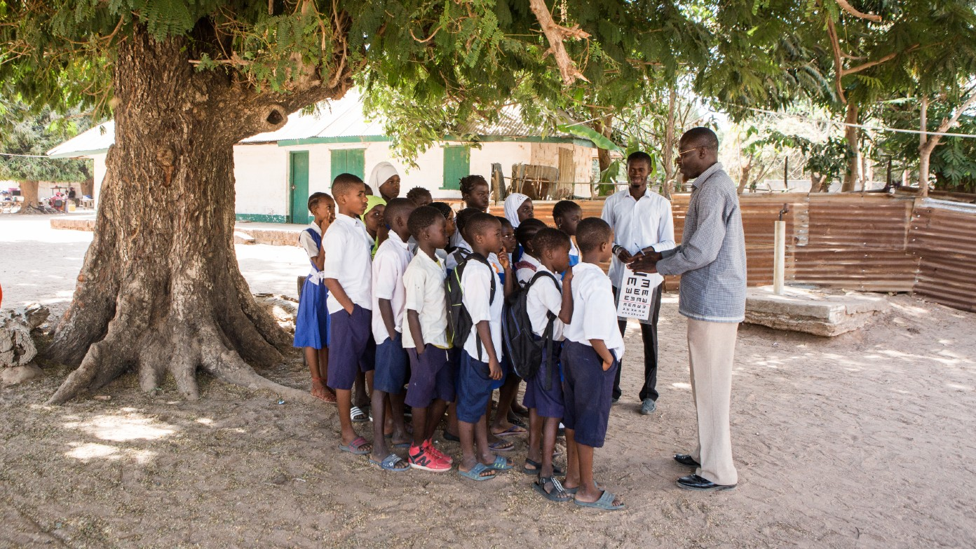 A man stands outside with a group of schoolchildren.